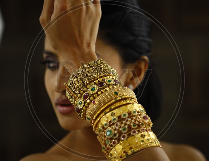 Woman model wearing different types of gold bangles and a pearl finger ring