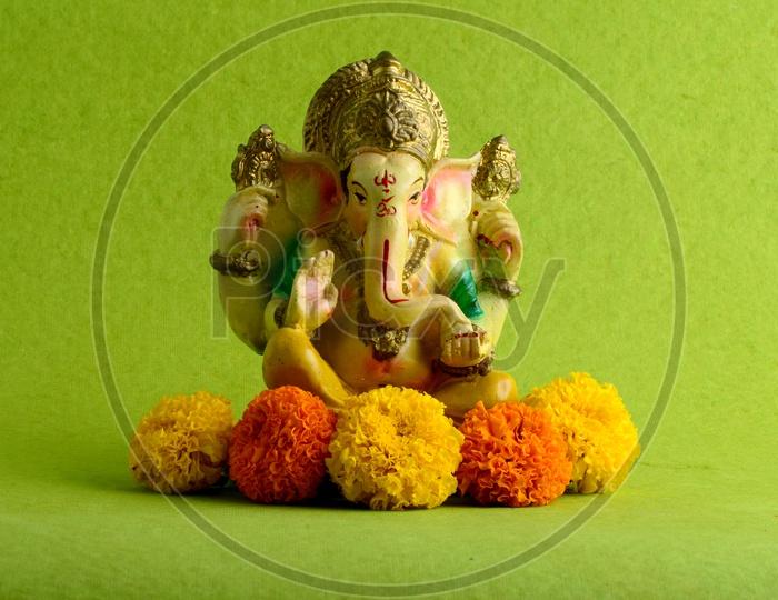 Hindu God Ganesha or Ganapathi. Lord Ganesha Idol on Green Background