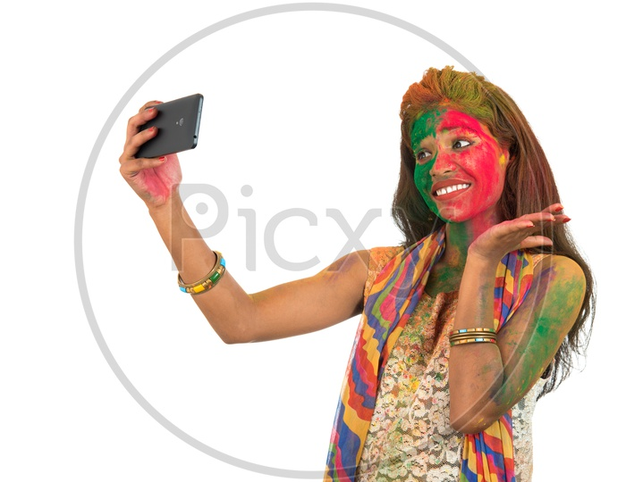 A Happy Young Indian Girl with Holi Colors On Her Taking Selfie With Smart Phone