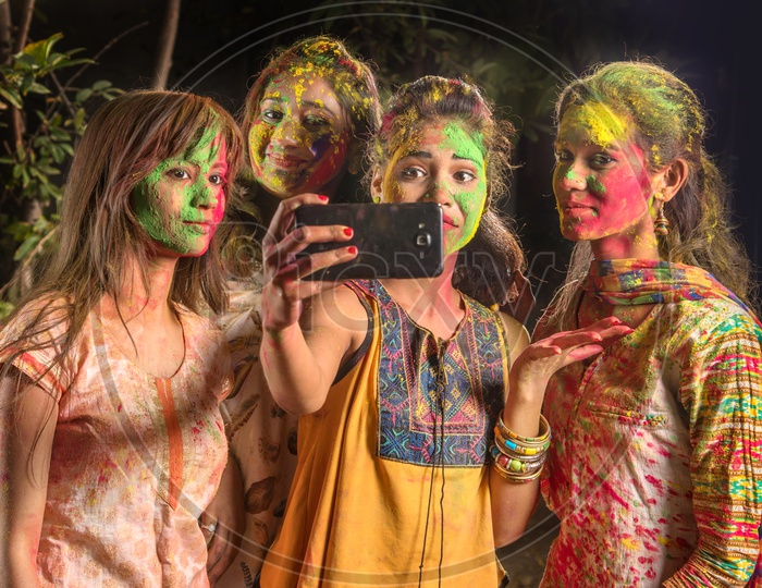 A Group Of Young Girls Filled In Holi Colors and Taking A Selfie In Smart Phone