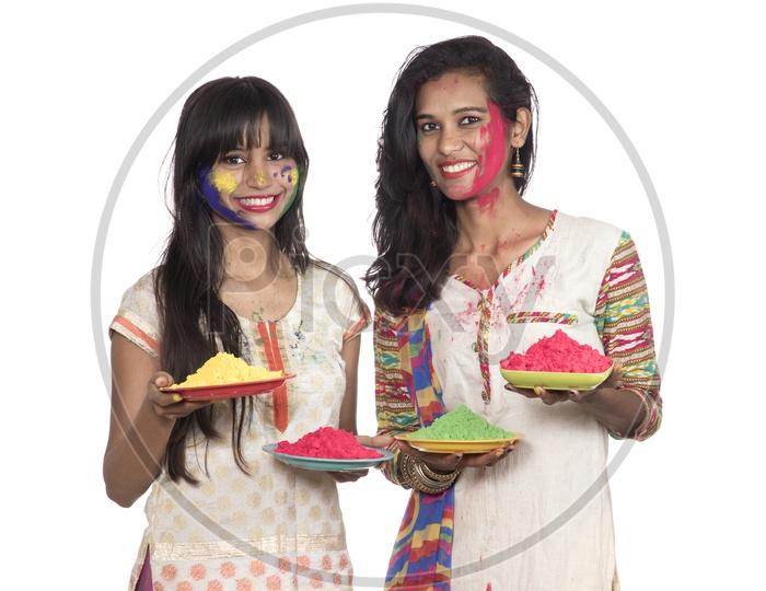 Young Indian Girls Holding Holi Color Powder Plates and Celebrating Holi