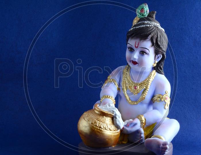 Little Krishna Idol on dark blue background