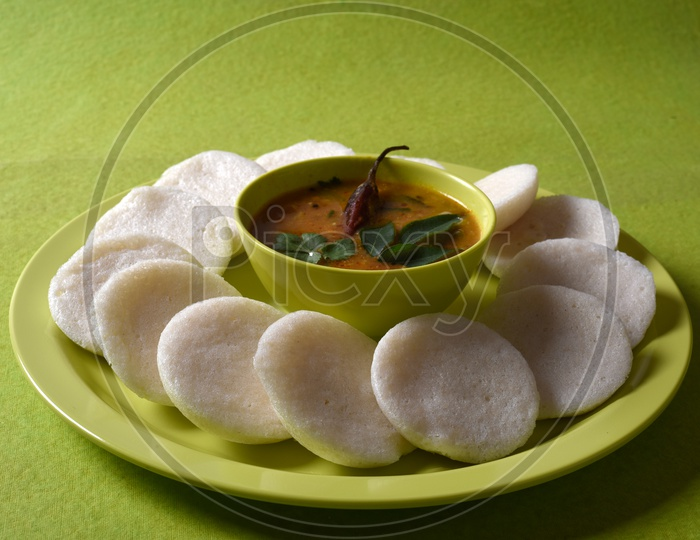 Idli with Sambar in bowl on green background