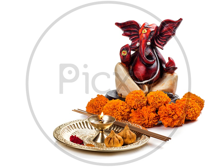 Lord Ganesh Idol with flowers and lightened up diya on white background
