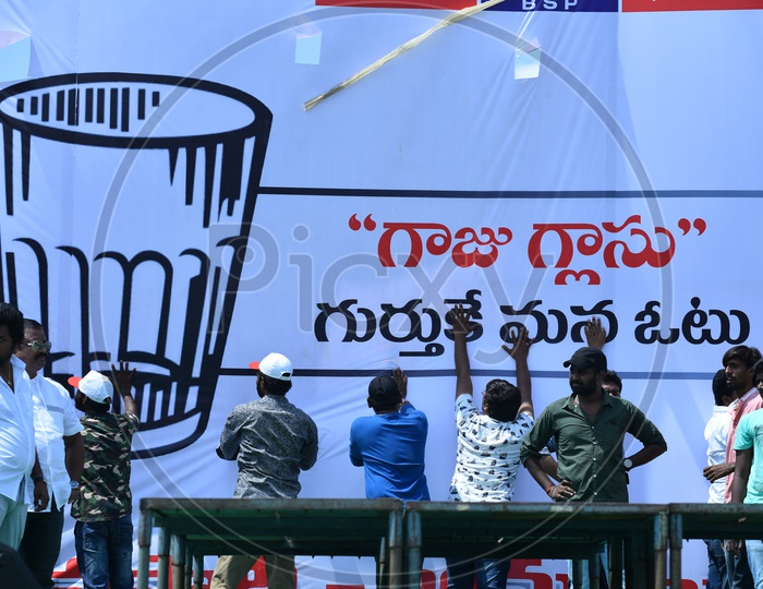Jana Sena party supporters setting up the banner at an election campaign in Amalapuram