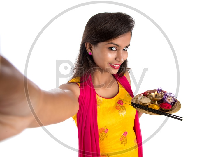 Beautiful Indian Girl Holding  Pooja Thali  Or Pooja Plate In Hand and Taken Selfie With Smart Phone
