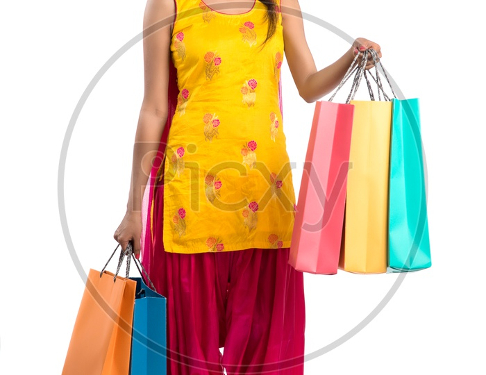 Beautiful Indian Girl holding Shopping Bags In Hand  and Posing Over a White Background