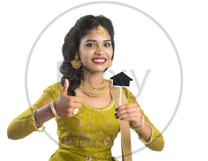 Happy Traditional Woman Holding A Little House Cutout Board in Her hand on an Isolated White Background