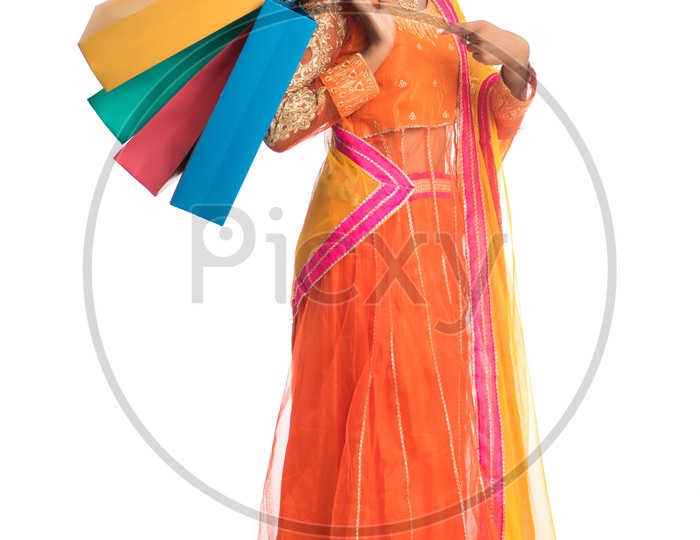 Young Indian Traditional  Girl Holding Shopping Bags Or Festival Shopping Bags And Posing On an Isolated White Background