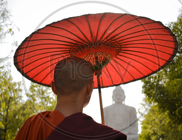 Monk looking at Buddha Statue