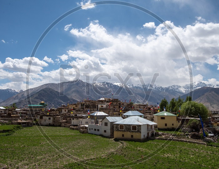 Snow capped Mountains of Spiti Valley with houses and agriculture fields