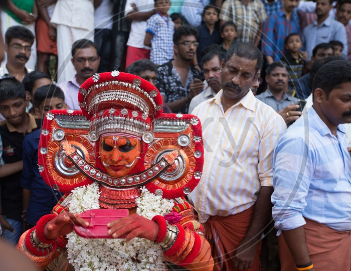 A Theyyam performer in colourful costume with a mirror