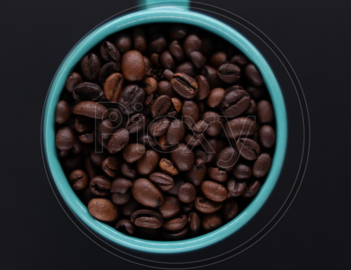 Coffee Beans In a Coffee Mug Composition On an Isolated Black Background