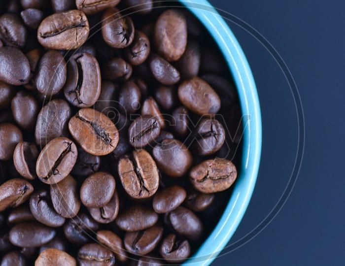 Coffee beans in a blue coffee mug on a black background
