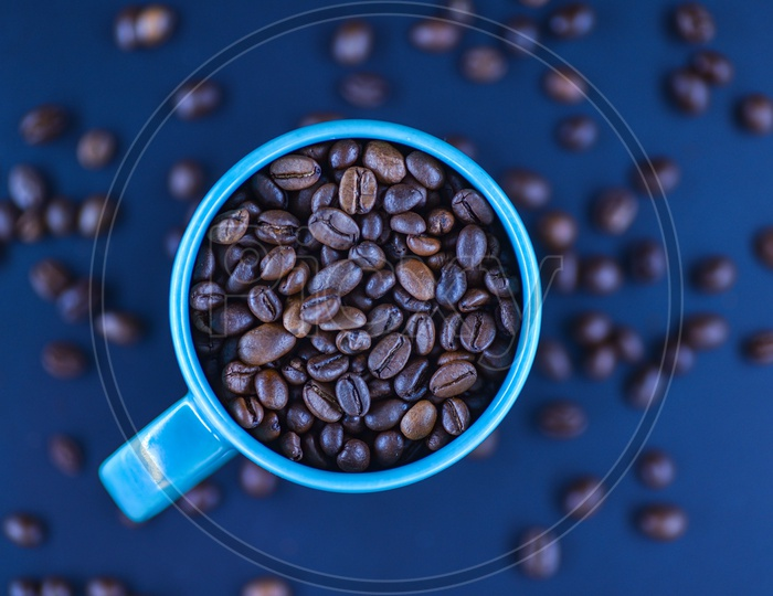 Coffee Beans In a Coffee Mug With Scattered Coffee Beans In Background