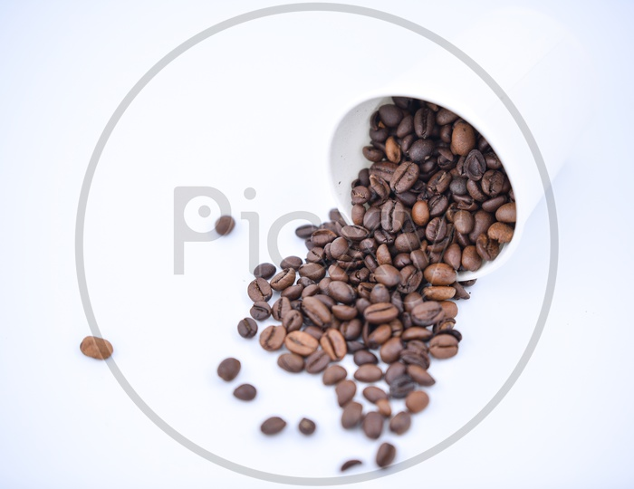 Coffee beans spilling out of a white take away cup on white background