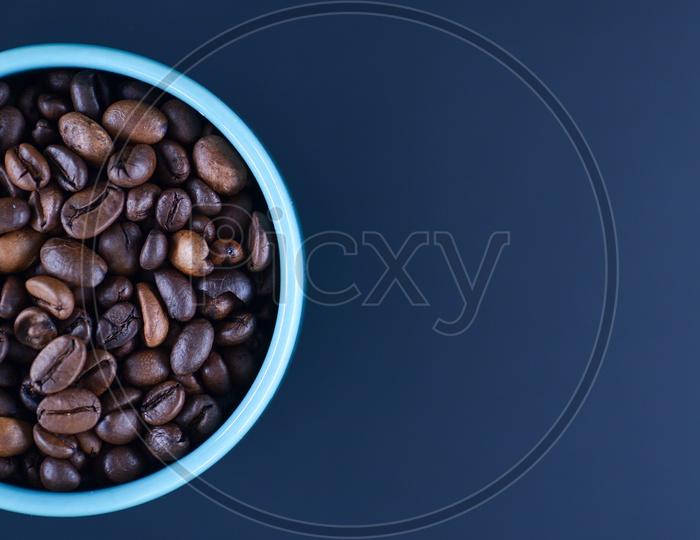 Coffee beans in a blue coffee mug on dark background