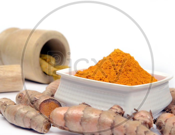 Organic Turmeric roots and Turmeric Powder in a bowl and wooden mortar, Indian spices