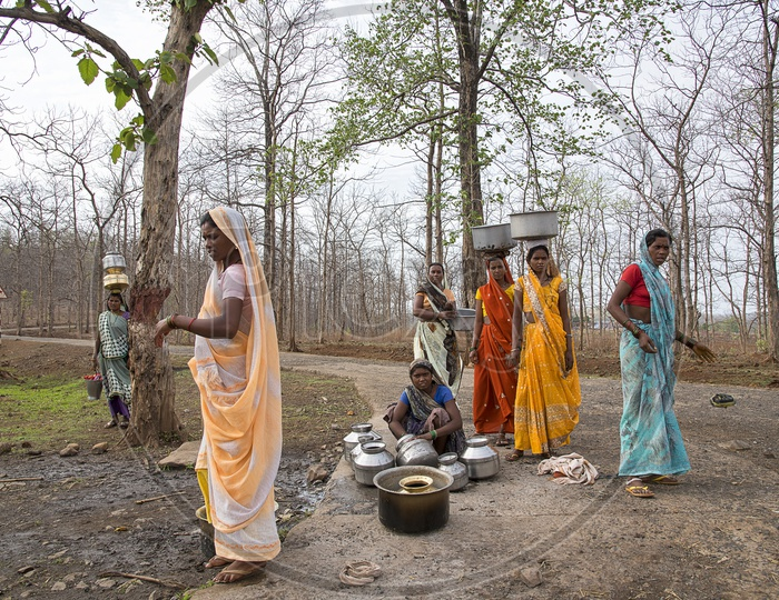 Unidentified rural Indian women carry water on their heads in traditional pots from hand pump, everyday Women walk few kilometers to get it due to drought.