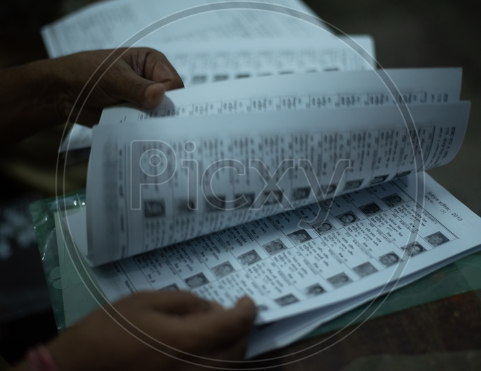 Polling Booth Officer Checking The Voter List And Verifying The Voter Slips in a Polling Booth