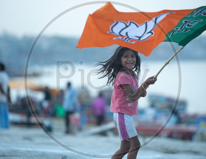 A Small Girl Waving  BJP Party Flag in Varanasi On Election Day