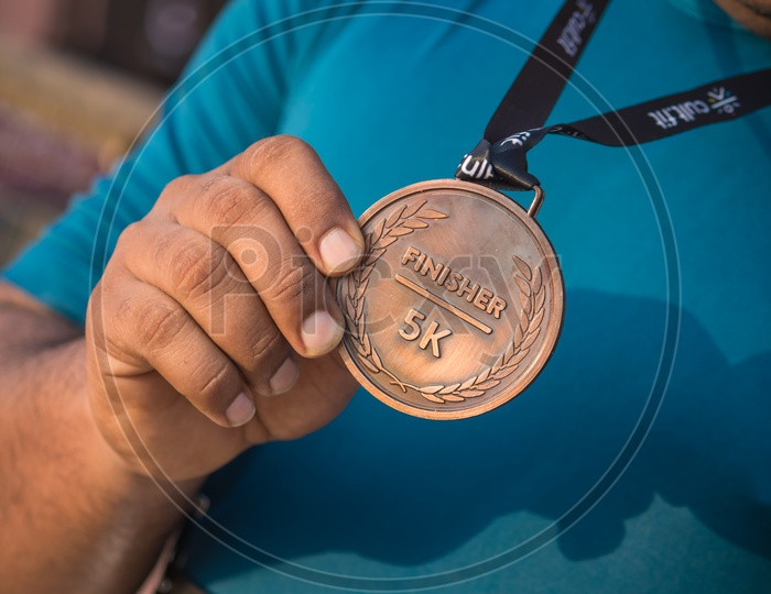 Close-up of athletes hand holding gold medal after victory in stadium