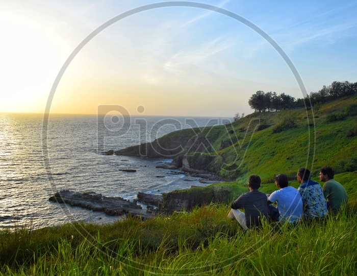 Friends  Watching And Enjoying  The Sunset Over  a  Sea Coast  From a  Hill Top