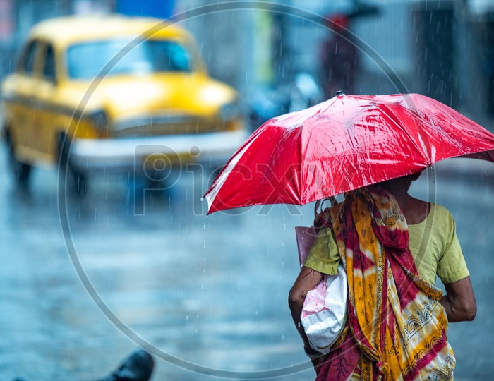 A woman walks holding an umbrella to cover herself from getting drenched as it rains heavily in Howrah,Kolkata.