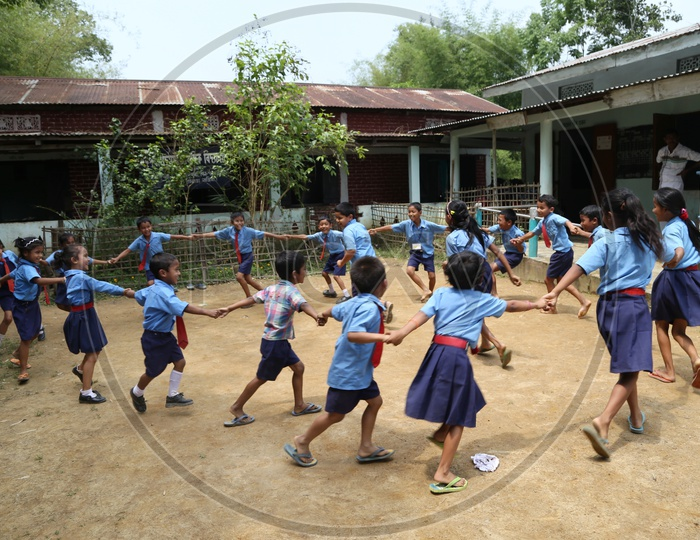 School children Or  School Students Wearing Uniforms And Playing Happily  in a Rural Village School Compound Or Premise