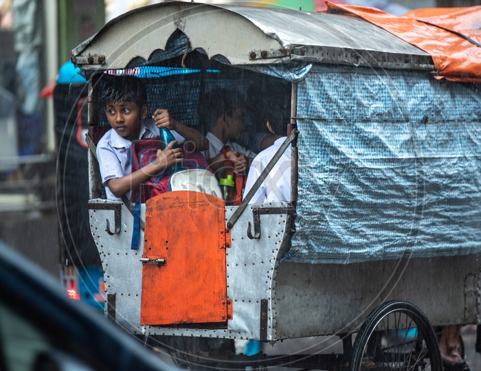 School Children In a Auto Going   To a School On a  Rainy  Day In Kolkata