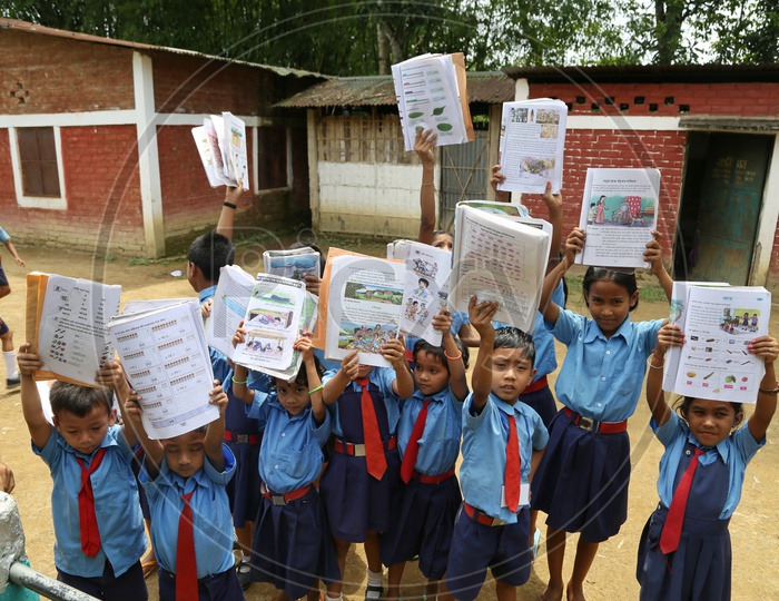 School children Or  School Students Wearing Uniforms And Holding Books In Hand   in a Rural Village School Compound Or Premise
