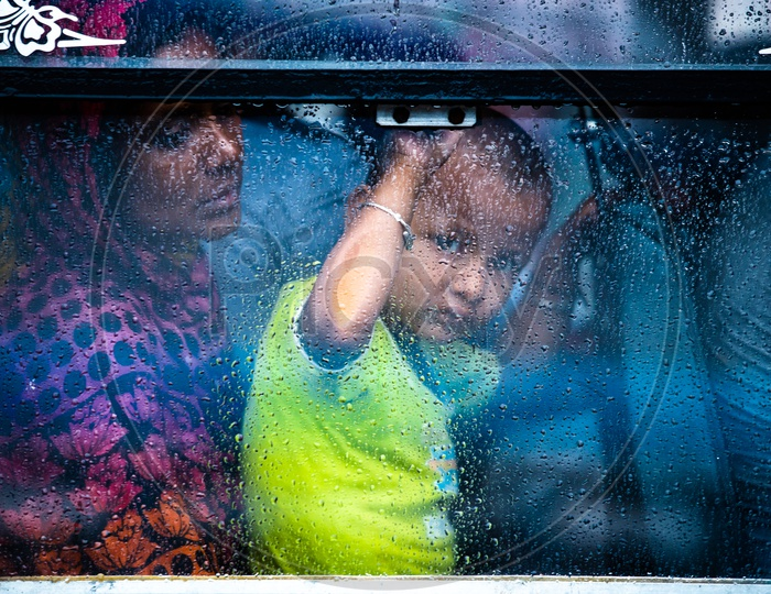 A Small  Child Looking Through The  Window Glass Of a   Bus While The  Rain Lashing Outside