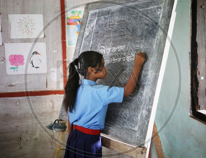 A  Girl Student  Writing On The  School Blackboard in A Classroom