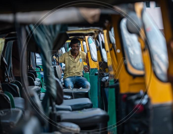 Auto Driver Of Green LPG  Auto   in  a Auto Stand