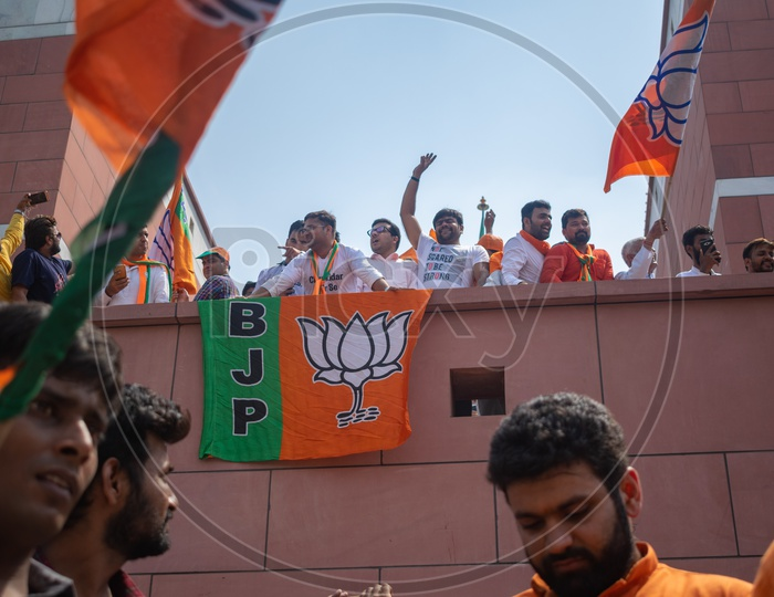 Flags of Bhartiya Janta Party (BJP) and people celebrating victory of the party