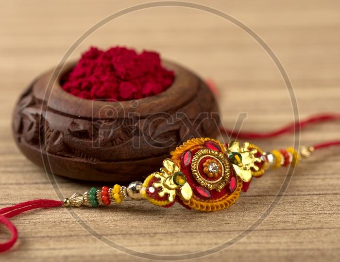 Indian festival: Raksha Bandhan background with an elegant Rakhi, Rice Grains and Kumkum.