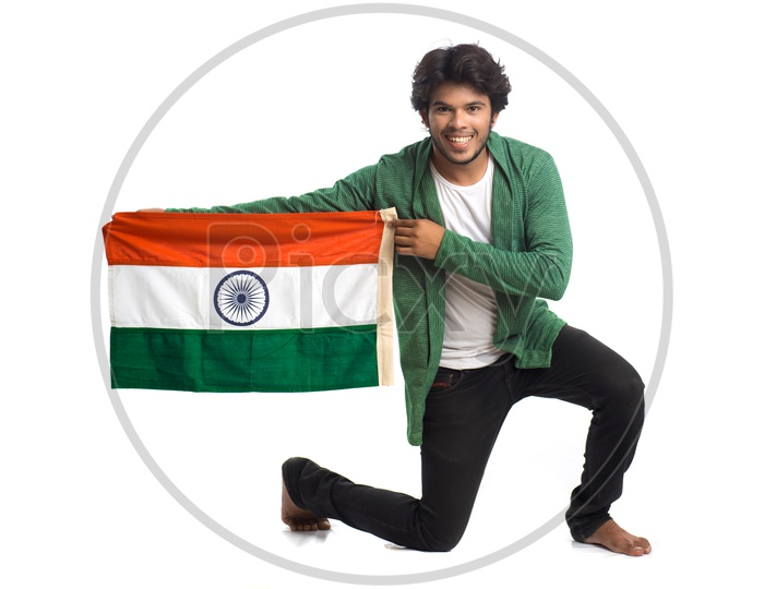 A Young Indian man Holding  Indian National Flag ( Tri Color )  In Hands And Posing Over a White Isolated Background