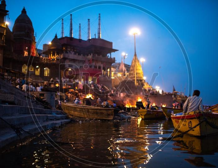 A Boat Rider Or Helmsman  At Manikarnika Ghat Watching The Burying of Dead Bodies  In Varanasi