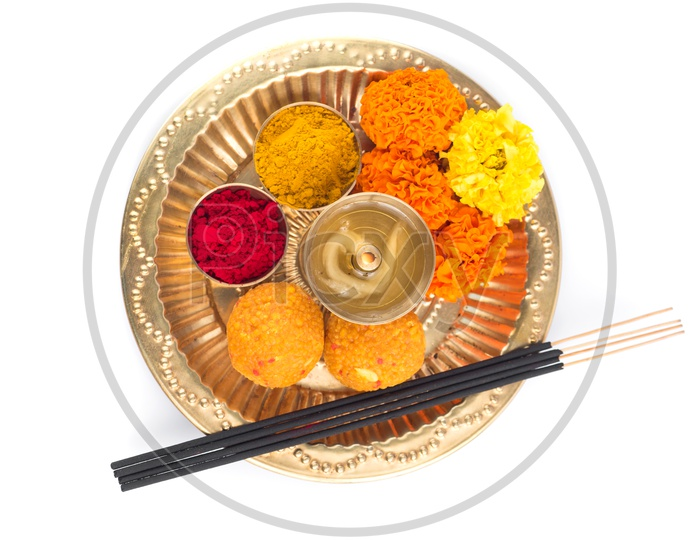 Indian Hindu Pooja Plates Or Thali With Diya , Kumkum , Sweet , Flower And Fragrance Sticks Or Agarbatti  On an Isolated White Background