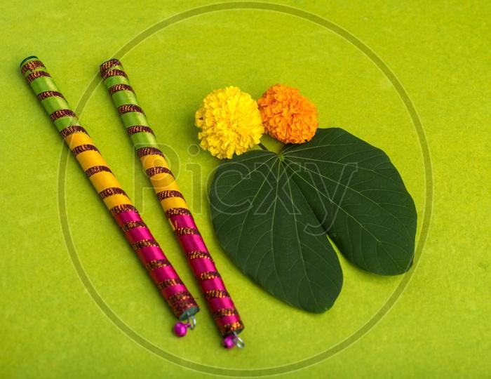 Indian Festival Dussera or Navrathri Symbolic Representation With Dandiya Sticks , Mari Gold Flowers And Golden Leaf ( Bauhinia Racemosa ) on an Isolated Background