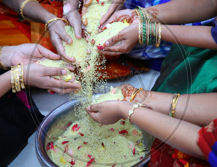 Woman Or Ladies Hands Mixing Turmeric Coated Rice  Or Akshintalu  In a Wedding Function