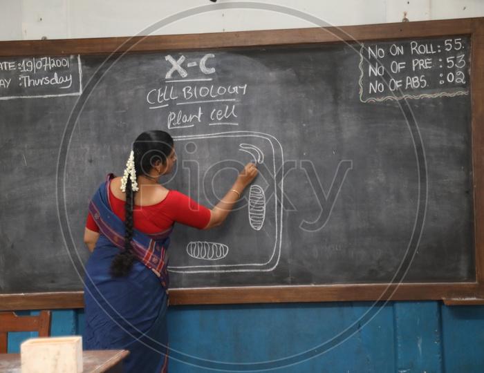 School teacher Writing On Blackboard In a Classroom