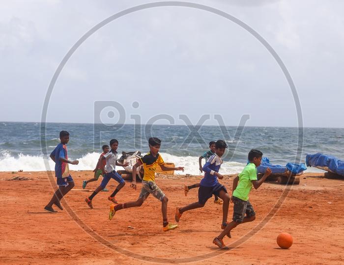 children playing football in beach