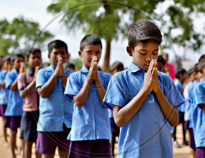 Govt school students performing morning prayer at school.