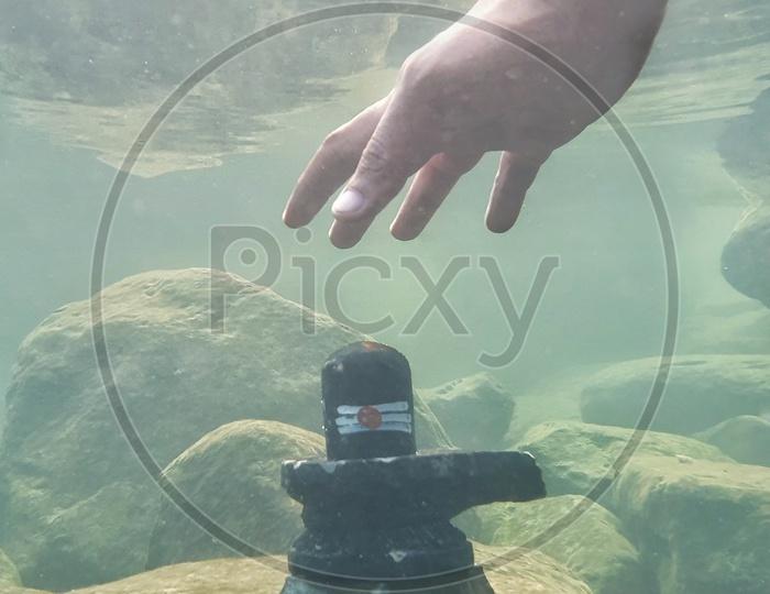 A Hand Touching  the Shiva Linga  Under Water Shot