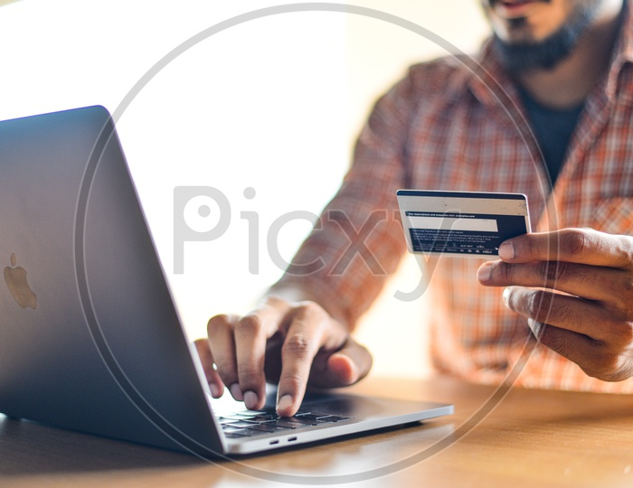 Online Payments Or Online Shopping  A Young Man Using Debit or Credit Card For Online Transaction or Payments in Laptop