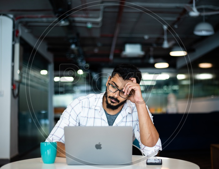 Frustrated Stressed Depressed Indian Professional Employee Young Man Student Holding Head in Hands Working on Laptop  in Office Work Space