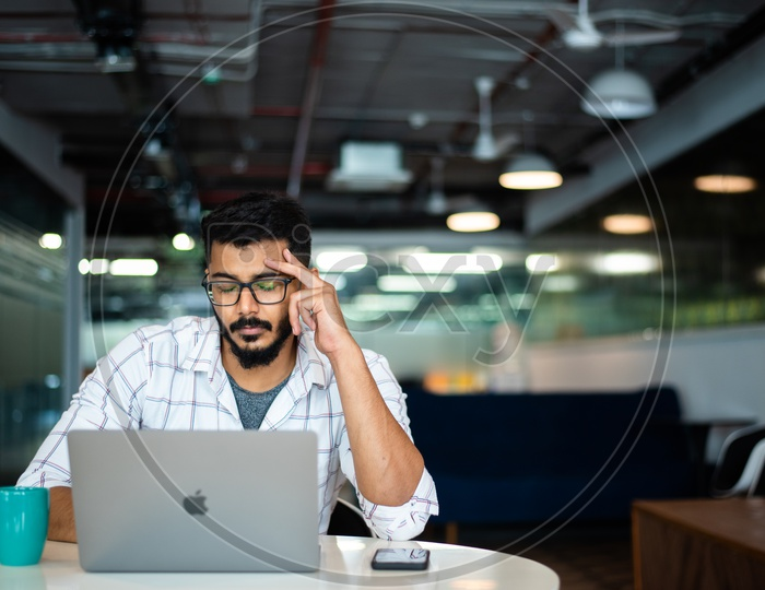 Frustrated Stressed Depressed  Indian Professional Young Man Employee Holding Head in Hands Working on Laptop  in Office Work Space