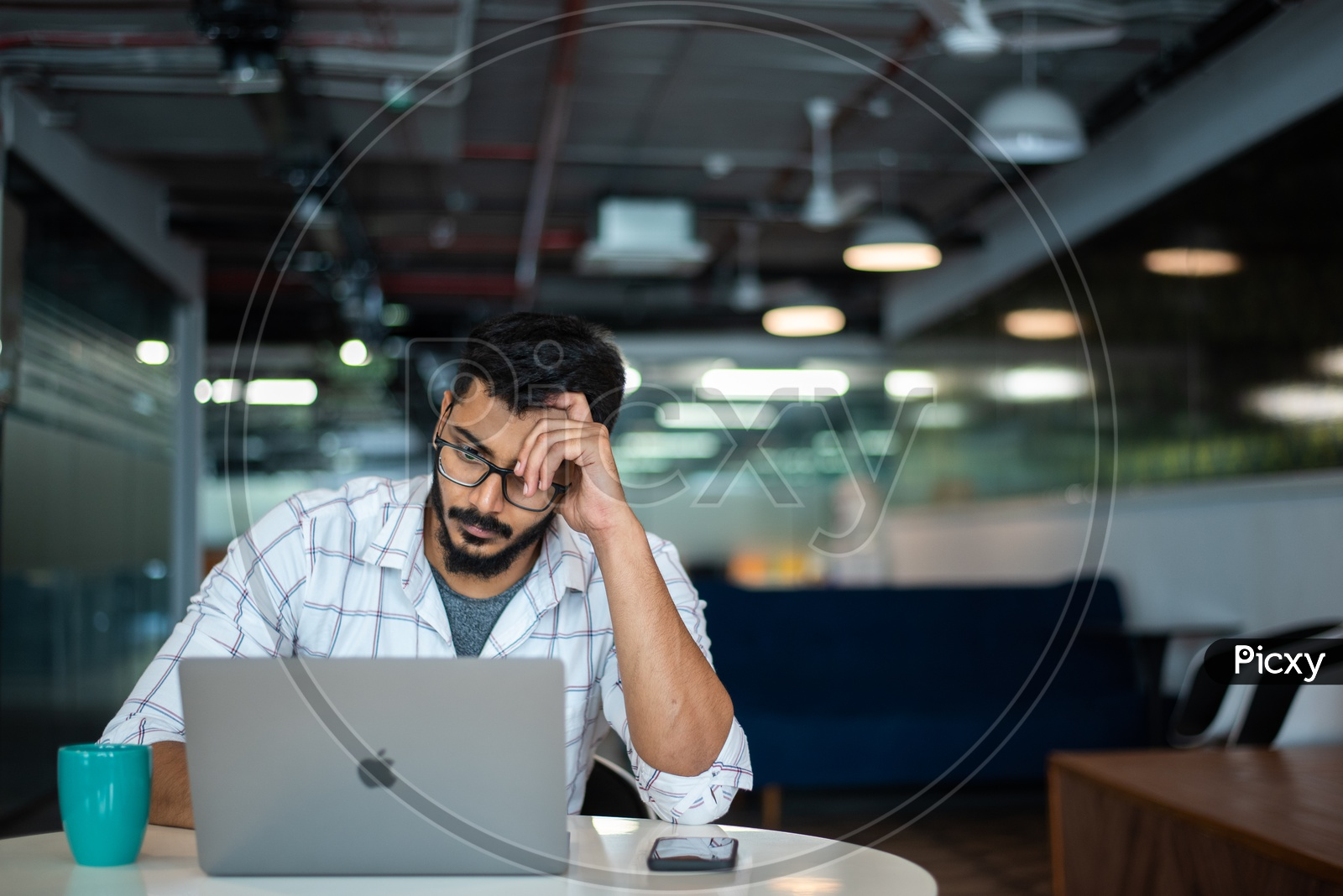 Frustrated Stressed Depressed Young Man Holding Head in Hands Working on Laptop  in Office Work Space