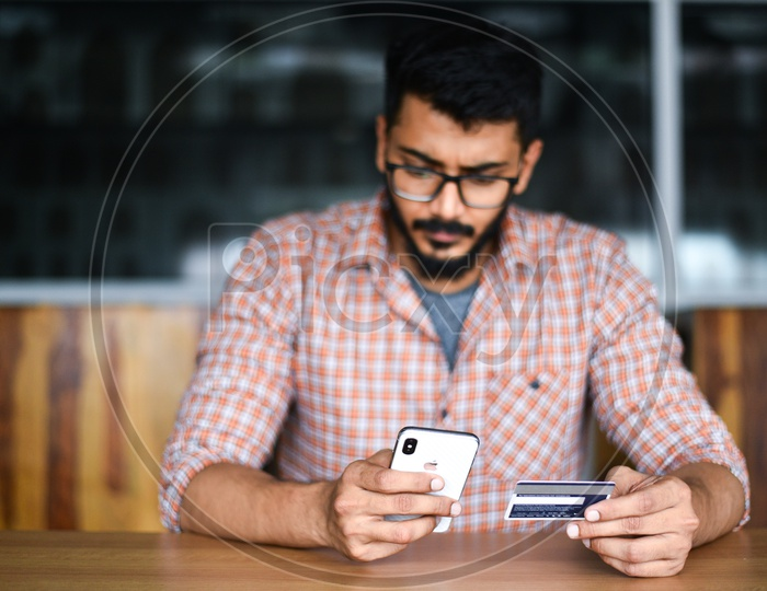 Online Payments Or Online Shopping  A Young Man Using Debit or Credit Card For Online Transaction or Payments in Smartphone or Mobile